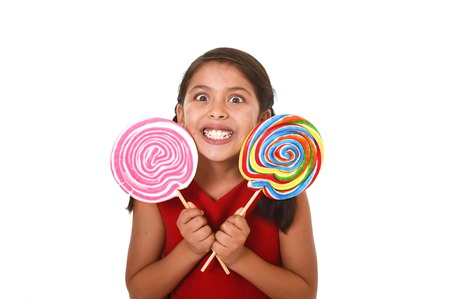 white sugar: happy female child wearing red dress holding two big lollipop in crazy funny face expression in sugar addiction and kid love for sweet candy concept isolated on white background