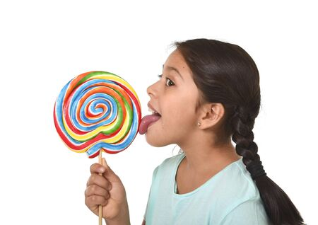 happy female child holding big lollipop candy licking the candy with her tongue in sugar addiction and kid love for sweet concept isolated on white background