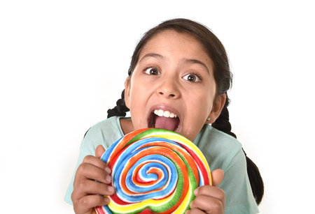 caramel candy: happy female child holding big lollipop candy licking the candy with her tongue in cheerful face expression in sugar addiction and kid love for sweet concept isolated on white background Stock Photo