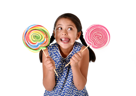 lolli: happy female child wearing dress holding two big lollipop in crazy funny face expression in sugar addiction and kid love for sweet candy concept isolated on white background