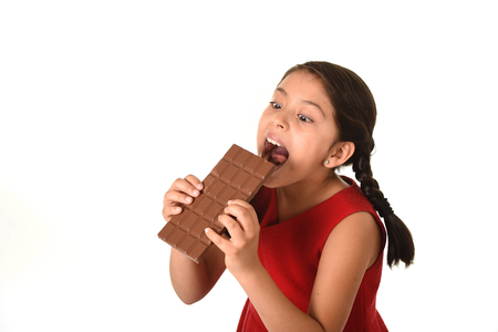8 years old: 7 or 8 years old Hispanic girl wearing red dress holding with both hands big biting chocolate bar eating in happy and excited face expression in sugary nutrition and kids loving sweet concept