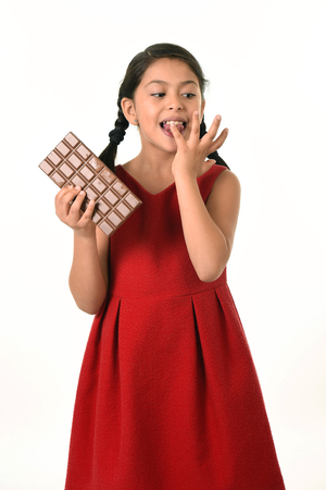 8 years old: 7 or 8 years old Hispanic girl wearing red dress holding big chocolate bar eating in happy and excited face expression licking her fingers in sugary nutrition and kids loving sweet concept