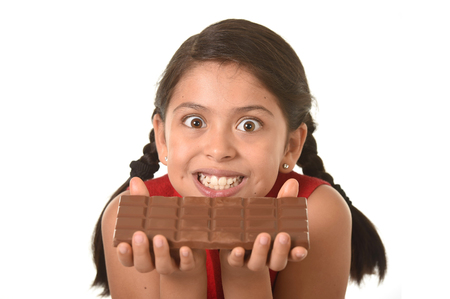 8 years old: 7 or 8 years old Hispanic girl wearing red dress holding with both hands big chocolate bar in front of her crazy excited face expression in sugary nutrition and kids loving sweet concept