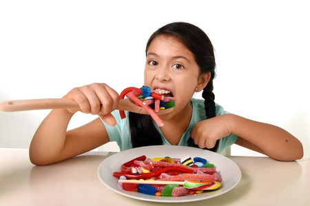 hispanic girl: happy excited Latin female child holding spoon eating from a dish full of candy , lollipop and sugary things in unhealthy sweet nutrition and kid in sugar abuse concept