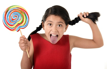 hispanic girl: happy female child in red dress holding big lollipop candy pulling her pony tail with crazy funny face expression in sugar addiction and kid love for sweet candy concept isolated on white background
