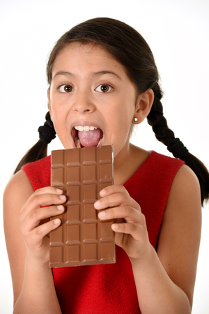 7 8 years: 7 or 8 years old Hispanic girl wearing red dress holding with both hands big chocolate bar eating in happy and excited face expression in sugary nutrition and kids loving sweet concept