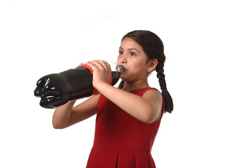 excess: happy female child holding big cola soda bottle drinking isolated on white background in sugar drink abuse and addiction and sweet nutrition excess Stock Photo