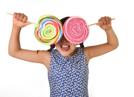 lolli: happy female child wearing dress holding two big lollipop in front of her face having fun in sugar addiction and kid love for sweet candy concept isolated on white background