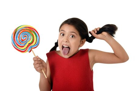 pony tail: happy female child in red dress holding big lollipop candy pulling her pony tail with crazy funny face expression in sugar addiction and kid love for sweet candy concept isolated on white background