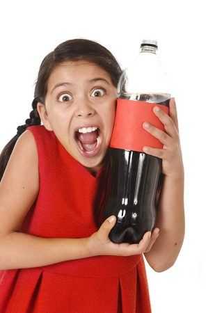 happy female child holding big cola soda bottle against her face in crazy and over excited expression isolated on white background in sugar drink abuse and addiction and sweet nutrition excess Stock Photo