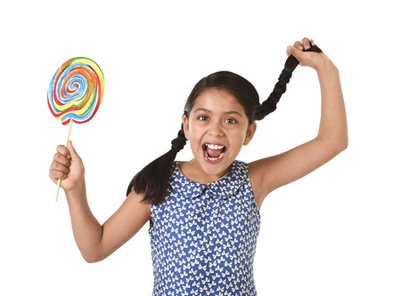 pony tail: happy female child holding big lollipop candy pulling her pony tail with crazy funny face expression in sugar addiction and kid love for sweet candy concept isolated on white background