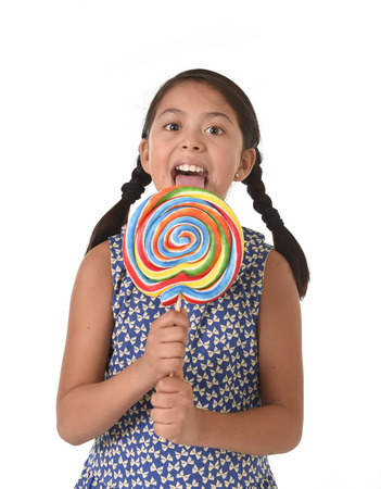 paleta de caramelo: feliz ni�a la celebraci�n de grandes caramelo del lollipop lamiendo el dulce con la lengua en la adicci�n de az�car y cabrito amor por concepto de dulce aislado en el fondo blanco