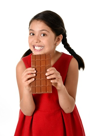 8 years old: 7 or 8 years old Hispanic girl wearing red dress holding with both hands big chocolate bar eating in happy and excited face expression in sugary nutrition and kids loving sweet concept