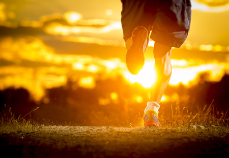 legs: close up image of young man strong legs off trail running at amazing summer sunset in sport and healthy lifestyle concept and jogging cross country training workout Stock Photo