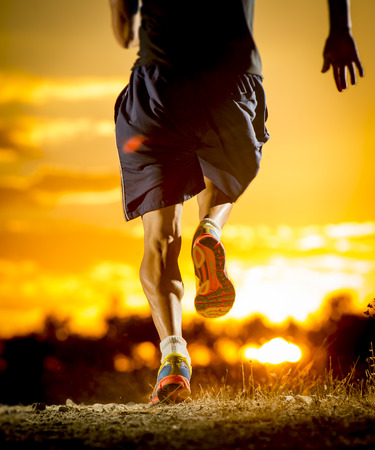 close up image of young man strong legs off trail running at amazing summer sunset in sport and healthy lifestyle concept and jogging cross country training workout Reklamní fotografie