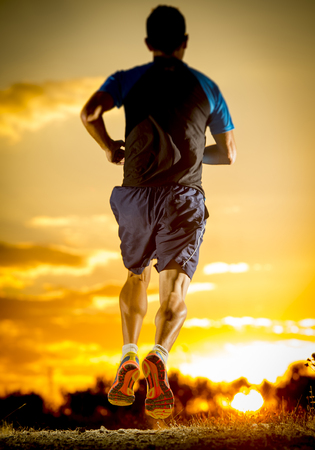 cross legs: close up image of young man strong legs off trail running at amazing summer sunset in sport and healthy lifestyle concept and jogging cross country training workout Stock Photo