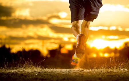 de cerca la imagen de hombre joven y piernas fuertes fuera de trail running en increíble atardecer de verano en el deporte y el concepto de estilo de vida saludable y trotar cruz sesión de entrenamiento de país Foto de archivo