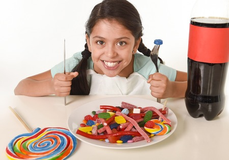happy Latin female child eating dish full of candy and gummies with fork and knife and big cola bottle in sugar abuse and sweet nutrition excess isolated on white background
