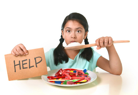 vulnerable: sad and vulnerable hispanic female child asking for help  eating dish full of candy and gummies holding sugar spoon in sweet abuse dangerous diet and unhealthy nutrition concept isolated on white