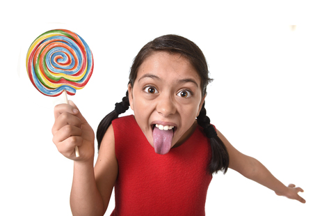 pretty pony: sweet beautiful latin female child holding big lollipop candy eating and licking happy and excited isolated on white background with tongue out in funny crazy face expression and sugar addiction concept Stock Photo