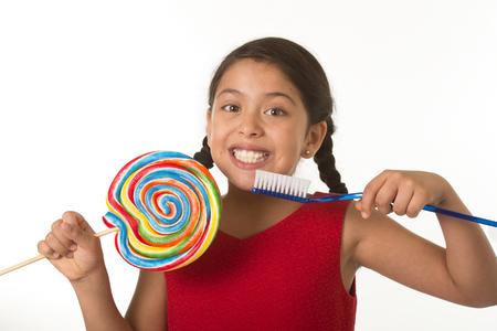 白い背景に分離されたかわいい女性子供の歯科医療と医療の概念と不健康な砂糖の乱用で大きなスパイラル棒付きキャンディーと巨大な歯ブラシを
