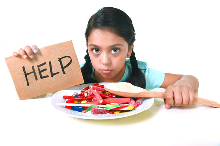 sugar spoon: sad and vulnerable hispanic female child asking for help  eating dish full of candy and gummies holding sugar spoon in sweet abuse dangerous diet and unhealthy nutrition concept isolated on white