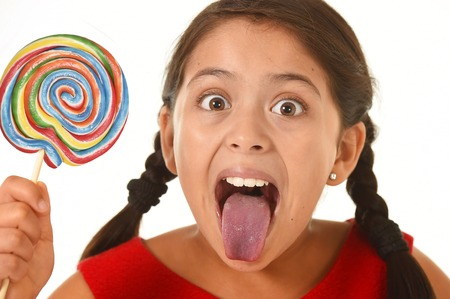 licking tongue: sweet beautiful latin female child holding big lollipop candy eating and licking happy and excited isolated on white background in funny crazy face expression and sugar addiction concept Stock Photo