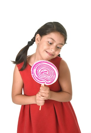lolli: sweet beautiful latin female child holding big pink spiral lollipop looking happy  isolated on white background in funny crazy face expression and sugar addiction concept Stock Photo
