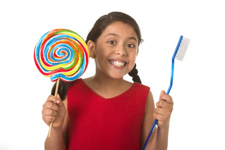 female child: cute female child holding big spiral lollipop candy and huge toothbrush in dental care and health concept and unhealthy sugar abuse isolated on white background Stock Photo
