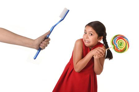 niños comiendo: linda niña la celebración de grandes caramelo del lollipop espiral y mano adulta que da a su enorme cepillo de dientes en el cuidado dental y el concepto de salud y el abuso de azúcar poco saludable aislado sobre fondo blanco