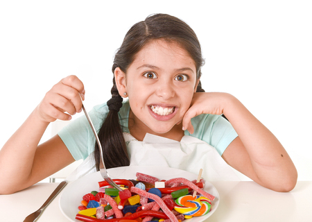excess: happy hispanic female child eating dish full of candy and gummies with fork and knife  in sugar excess and sweet nutrition abuse isolated on white background Stock Photo