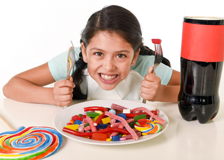 white sugar: happy Latin female child eating dish full of candy and gummies with fork and knife and big cola bottle in sugar abuse and sweet nutrition excess isolated on white background