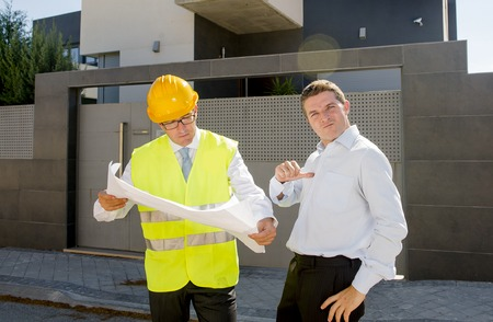 housing industry: happy customer smiling giving thumb up and constructor foreman worker with helmet and vest  outdoors proud on his new house building blueprints in real state business and housing industry concept Stock Photo