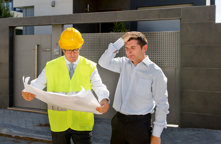 real state: unhappy customer in stress and constructor foreman worker with helmet and vest arguing outdoors on new house building blueprints in real state business bankrupt and housing industry concept Stock Photo
