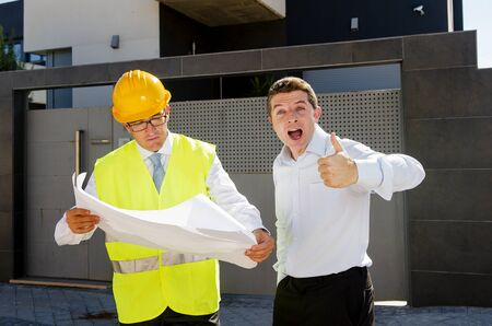 housing industry: happy customer smiling giving thumb up and constructor foreman worker with helmet and vest talking outdoors on new house building blueprints in real state business and housing industry concept Stock Photo