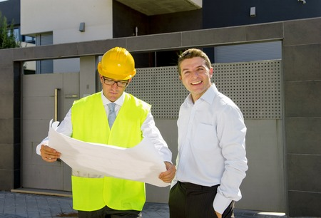 housing industry: happy customer smiling and constructor foreman worker with helmet and vest  talking outdoors on new house building blueprints in real state business and housing industry concept Stock Photo