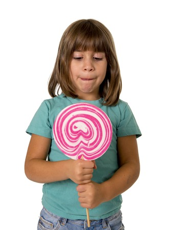 5 years old: 4 or 5 years old child girl eating big pink lollipop candy isolated on white background in children love sweet and sugar concept