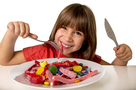 junk: cute European female child smiling happy eating candy like crazy with fork and knife in sugar abuse , unhealthy sweet nutrition concept , children candy addiction and kids  dental care Stock Photo