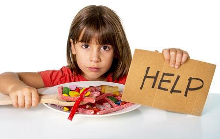 5 years old: sad and vulnerable 4 or 5 years old female child asking for help  eating dish full of candy holding sugar spoon in sweet abuse dangerous diet and unhealthy nutrition concept isolated on white Stock Photo