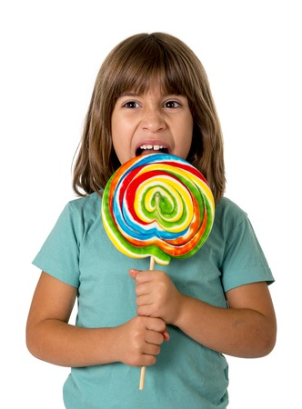 5 years old: 4 or 5 years old child girl eating big multicolor spiral lollipop candy isolated on white background in children love sweet and sugar concept and dental health and care concept