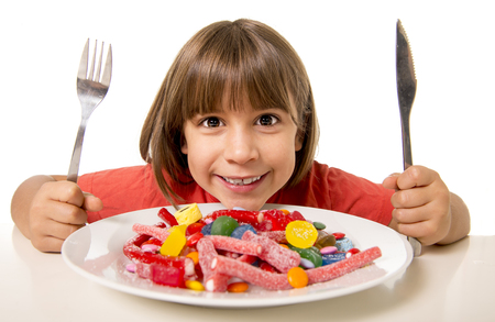 golosinas: linda niña Europea sonriente feliz comiendo dulces con tenedor cuchara y cuchillo en el abuso de azúcar, poco saludable concepto de nutrición dulce, los niños adicción a los dulces y los niños el cuidado dental