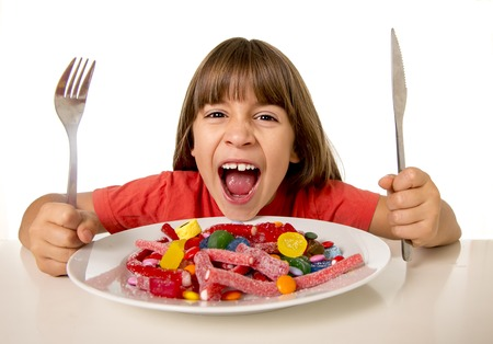 sweet food: cute European female child smiling happy eating candy like crazy with fork and knife in sugar abuse , unhealthy sweet nutrition concept , children candy addiction and kids  dental care Stock Photo
