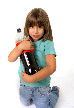 bad habit: little female child holding big cola soda bottle looking vulnerable in children sugar addiction and bad habit nutrition concept isolated on white background