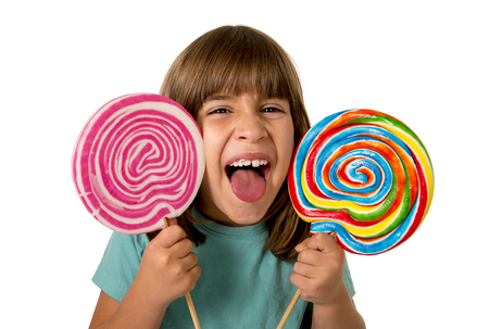 beautiful and happy female child having fun eating big lollipop spiral candy with  funny face expression isolated on white background in kid sugar abuse and excess concept