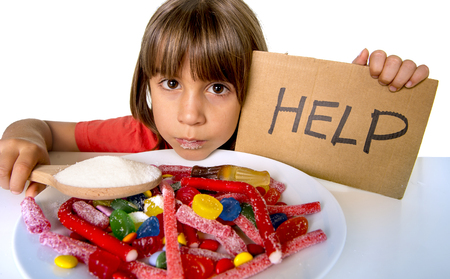 sad and vulnerable 4 or 5 years old female child asking for help  eating dish full of candy holding sugar spoon in sweet abuse dangerous diet and unhealthy nutrition concept isolated on white Stock Photo