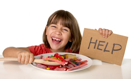 5 years old: happy vulnerable 4 or 5 years old female child asking for help  eating dish full of candy holding sugar spoon in sweet abuse dangerous diet and unhealthy nutrition concept isolated on white