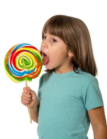 paletas de caramelo: 4 o 5 años del niño que come y lamer con la lengua caramelo grande Lollipop espiral multicolor aislado en el fondo blanco en los niños el concepto de amor dulce y el azúcar y la salud dental y cuidado concepto Foto de archivo