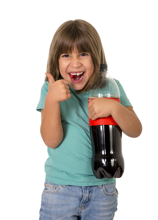 bad habit: little female child giving thumb up holding big cola soda bottle smiling happy in children sugar addiction and bad habit nutrition concept isolated on white background Stock Photo