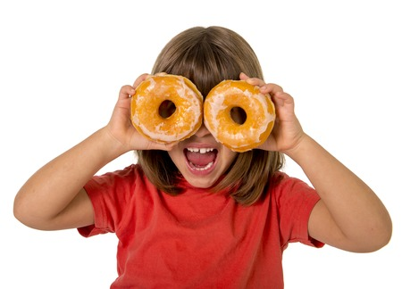 child laughing: happy female child having fun playing with two sugar donuts in the eyes smiling excited isolated on white background in children love sweet cakes and bakery concept Stock Photo
