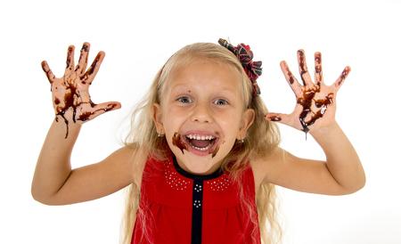 Bonita niña con el pelo rubio y ojos azules largas que llevan vestido de color rojo con la boca y las manos sucias con manchas de jarabe de chocolate después de comer torta sonriente feliz aisladas sobre fondo blanco Foto de archivo - 46548985